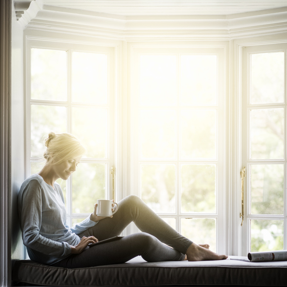 A woman sits in a sunny window.